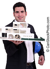 Architect holding up a building model