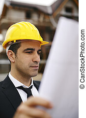 Architect in construction site looking at building plans