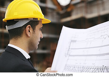 Architect in construction site looking at building plans -...