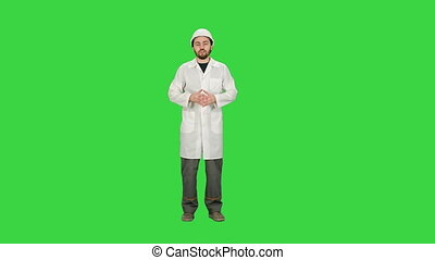 Architect in helmet talking to camera on a Green Screen, Chroma Key.