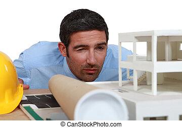 Architect inspecting model housing