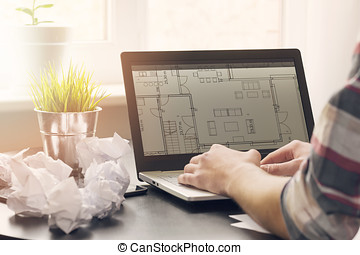 architect, interior designer working on laptop with floor plans