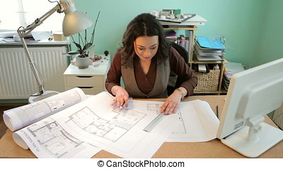 Architect is working with blueprints in her office