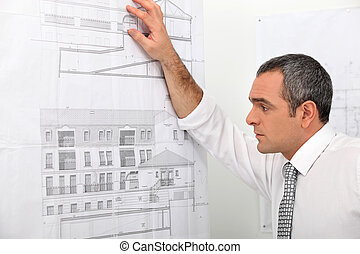 Architect looking at blueprints stuck to wall
