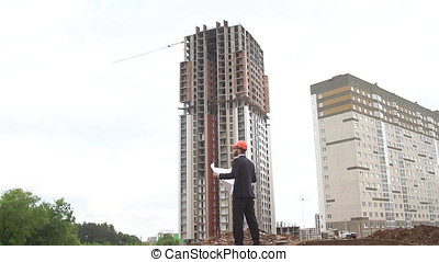 Architect looking at building plans with new construction