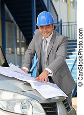 Architect looking at plans on a car bonnet
