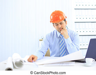 Architect looking working in office at desk. Wearing hardhat and taking notes on paper