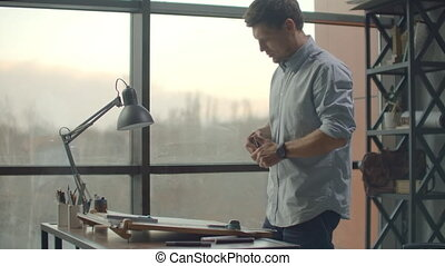 Architect man sits at drafting table in modern industrial office during the day