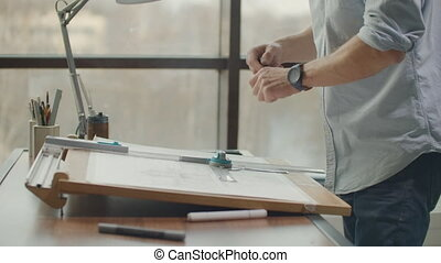 architect man Standing working with blueprints sketching a construction project on wood desk at home office. Construction design concept. vintage color tone.