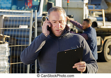architect on building site using mobile phone