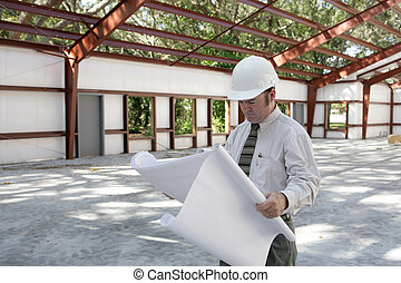Architect on Jobsite - An architect going over blueprints on...