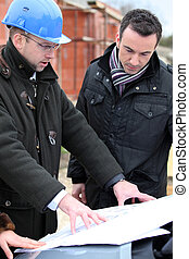 Architect on site with plans