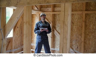 Architect or builder check plans in a half built timber frame house. Engineer on the construction of a frame wooden house. 4k 60fps slow motion