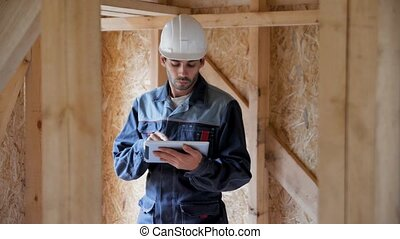 Architect or builder check plans in a half built timber frame house. Engineer on the construction of a frame wooden house. 4k close up