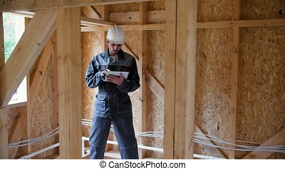 Architect or builder check plans in a half built timber frame house. Engineer on the construction of a frame wooden house. 4k