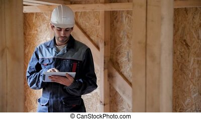 Architect or builder check plans in a half built timber frame house. Smiling Builder on a construction site with a tablet. 4k