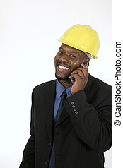 Smiling architect, engineer, or supervisor in yellow hardhat talking on a cellphone.