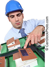 Architect pointing to solar panel on model house