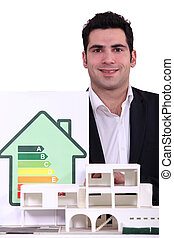 architect posing near model shows house with energy rating