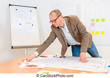 Architect Reaching For Document While Working On Blueprint