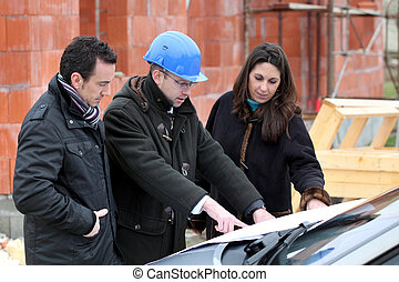 Architect reviewing a building plan with his clients