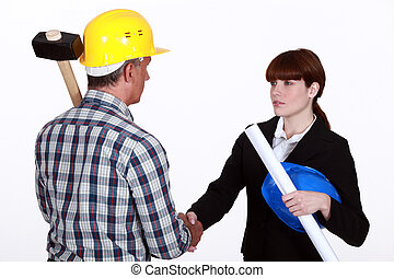 Architect shaking hands with a construction worker