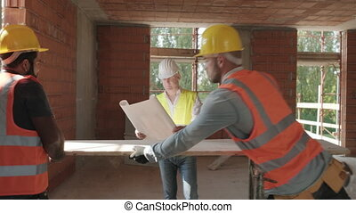 Architect Showing Building Plans To Workers In Construction Site