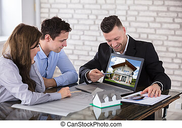 Architect Showing House Model To Couple In Office