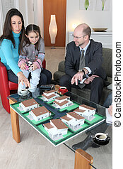 Architect showing model housing to mother and daughter