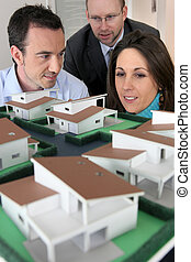 Architect showing scale model of house to buyers