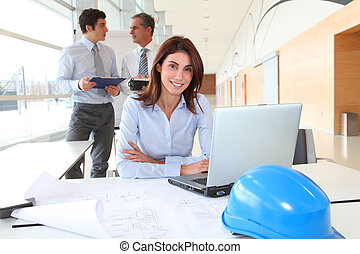 Architect sitting in front of laptop computer