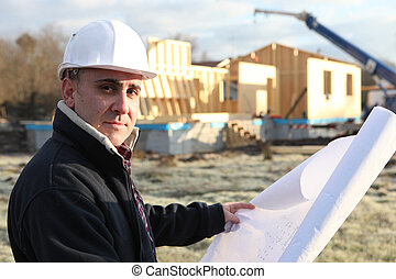 Architect stood with unfinished house in the distance