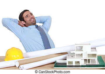 Architect stretching at his desk