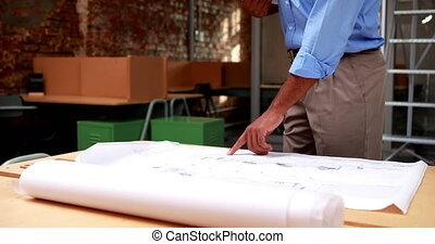 Architect studying blueprints