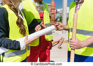 Architect talking with the workers about the implementation of t