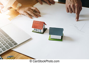 Architect Team Brainstorming Planning Design, Civil engineer sketching a blueprint of construction project with small house model and safety helmet in office, Construction Concept.