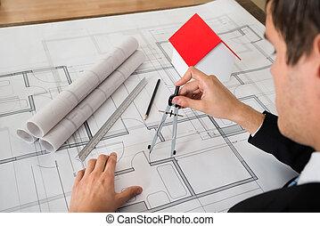 Architect Using Compass On Blueprint