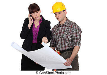 Architect with a builder and plans