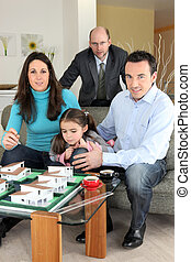 Architect with a family looking at a construction model