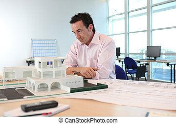 Architect with a model of a building