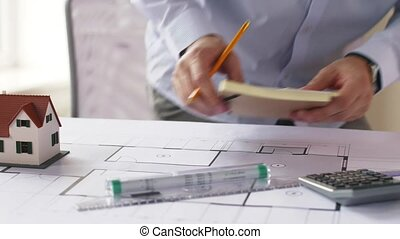 architect with blueprint and stickers taking notes