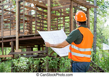 Architect With Blueprint At Construction Site