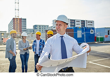 architect with blueprint on construction site