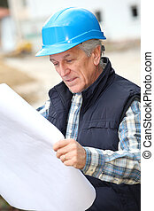 Architect with drawing on construction site
