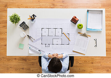 architect with house blueprint at office