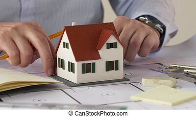 architect with house model and blueprint