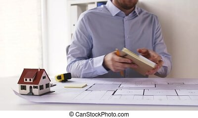 architect with notebook, blueprint and palettes