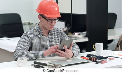 Architect with safety helmet using electronic tablet in the office