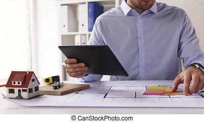 architect with tablet pc, blueprint and palettes -...