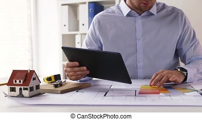 architect with tablet pc, blueprint and palettes